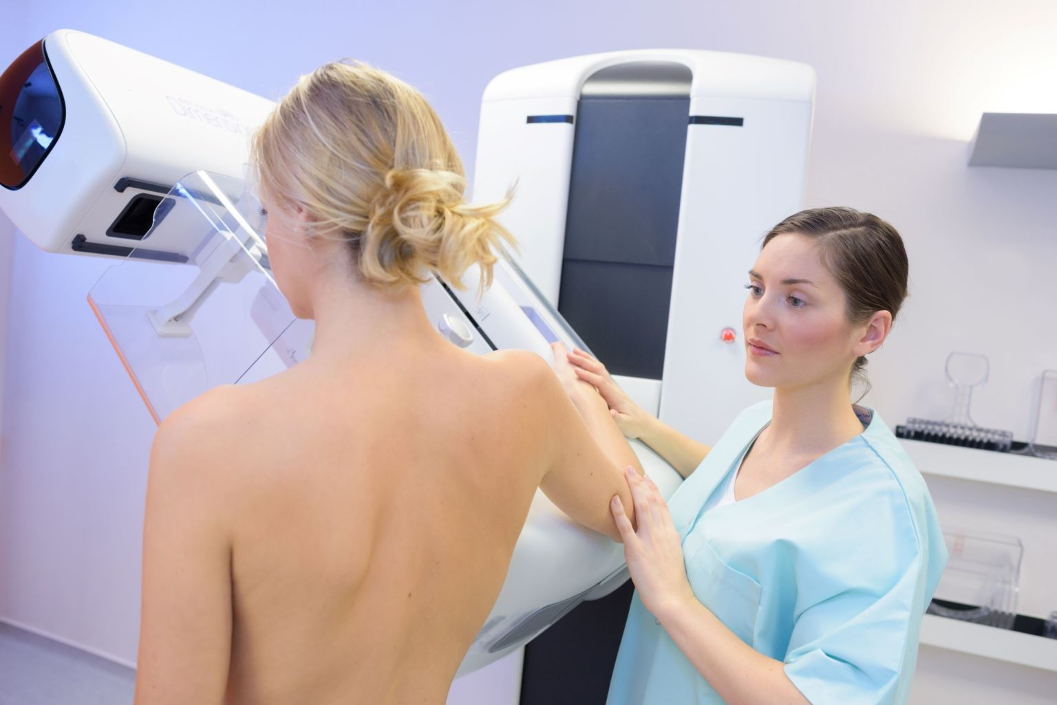 Kvinna och sjuksköterska vid röntgenapparat.