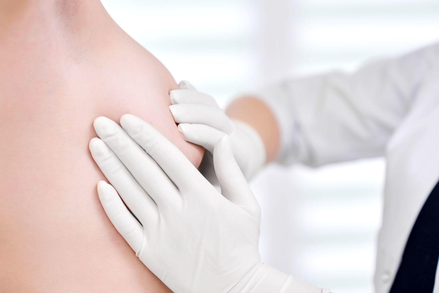 Händer med handskar undersöker ett bröst.