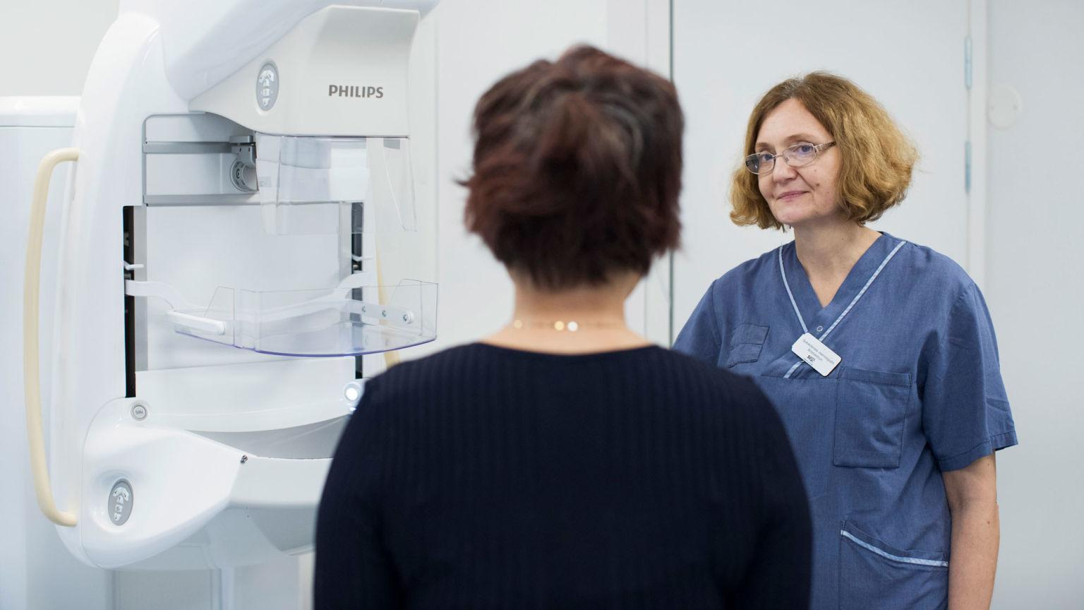 Kvinna på mammografiundersökning framför en röntgenapparat.