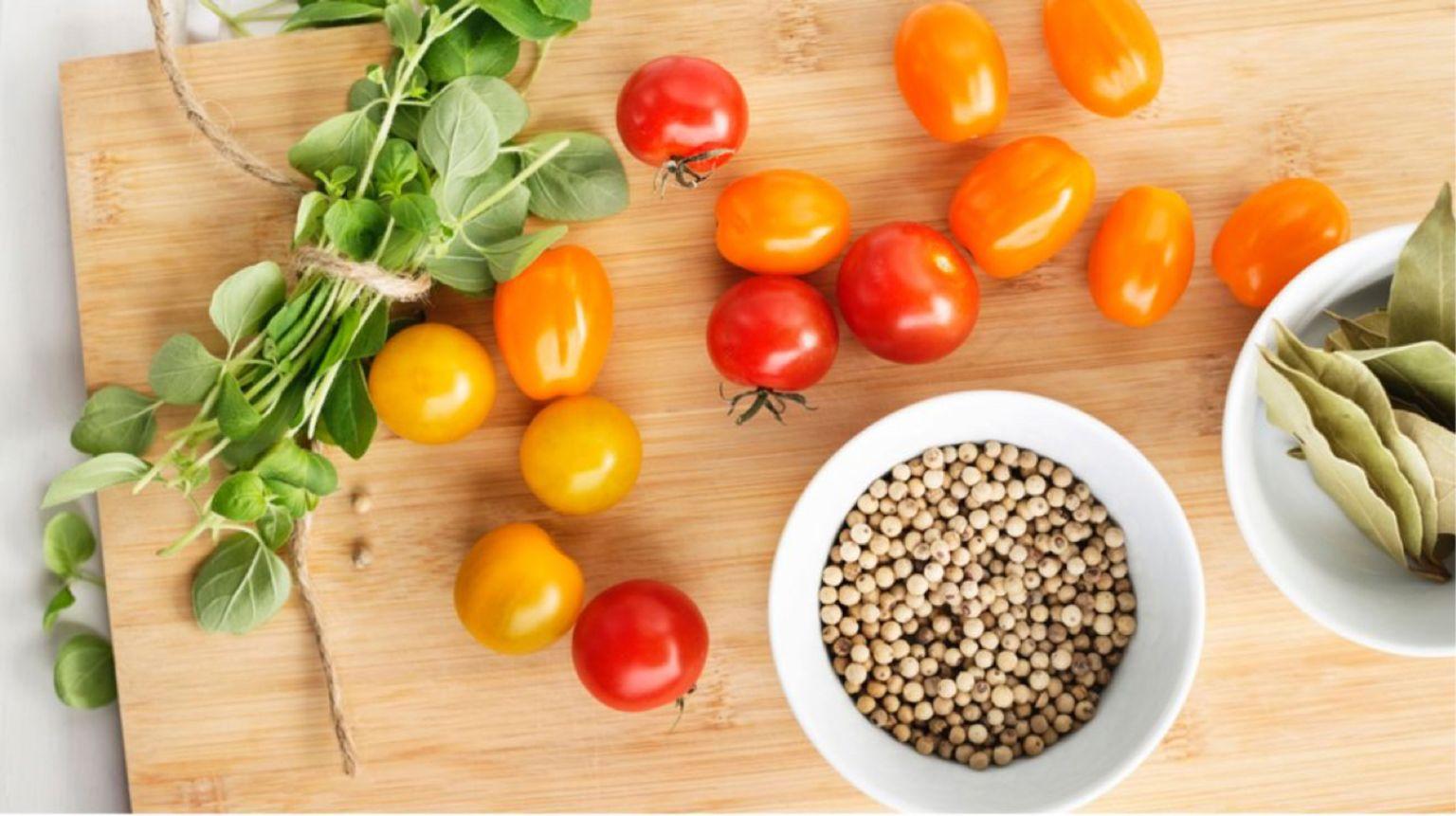 Tomater, bönor och grönsaker ligger utplacerade på en skärbräda