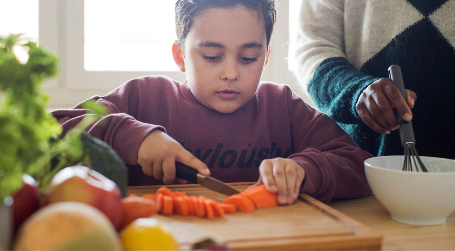Pojke sitter och skär grönsaker på en skärbräda.