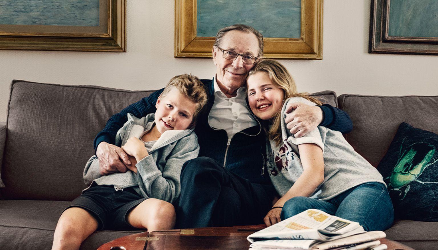 Morfar sitter i en soffa med barnbarn.