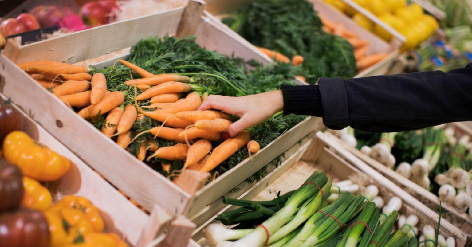 En hand sträcker sig efter morötter i grönsaksdisken
