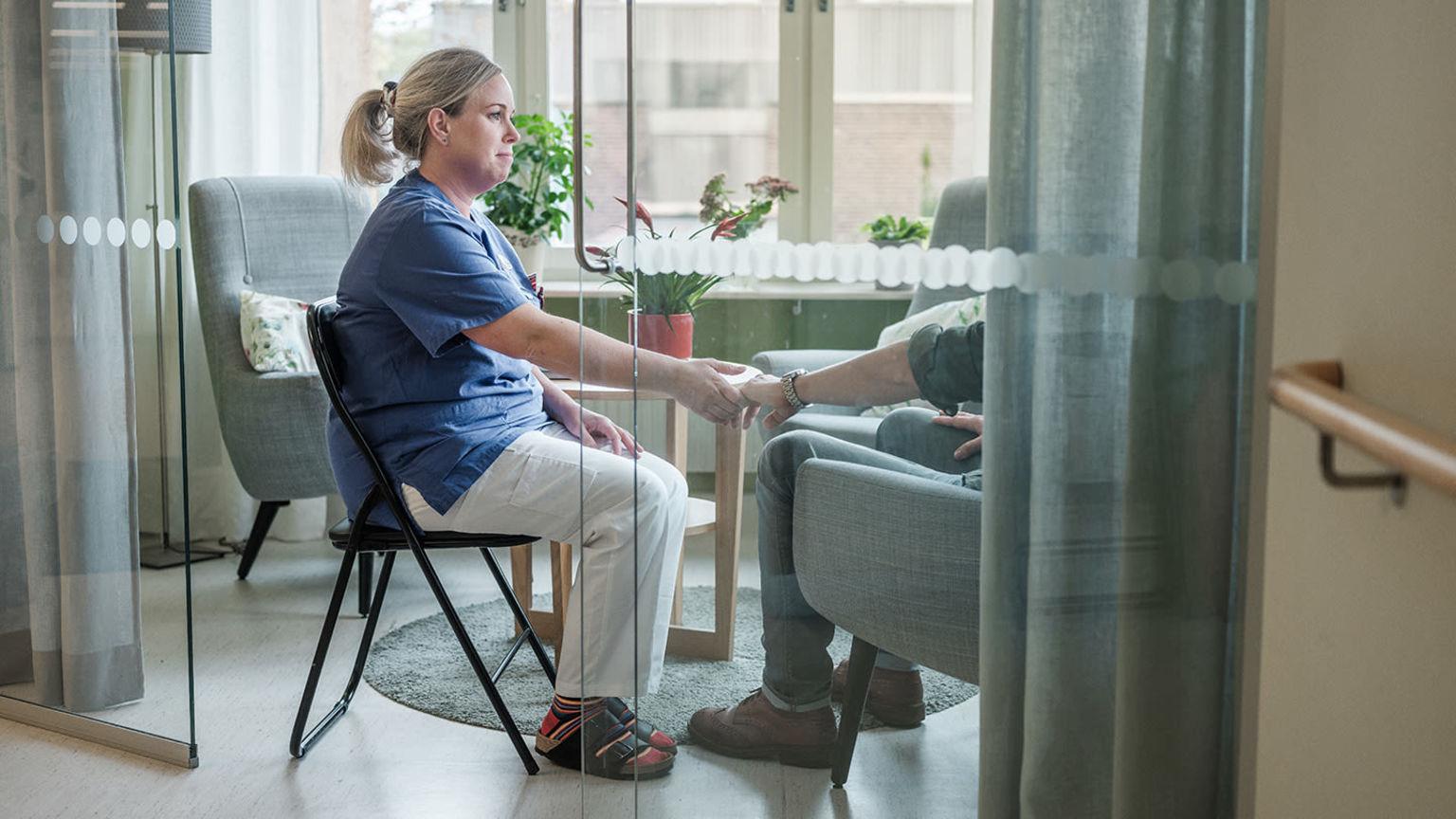 Sjuksköterska håller handen på patient