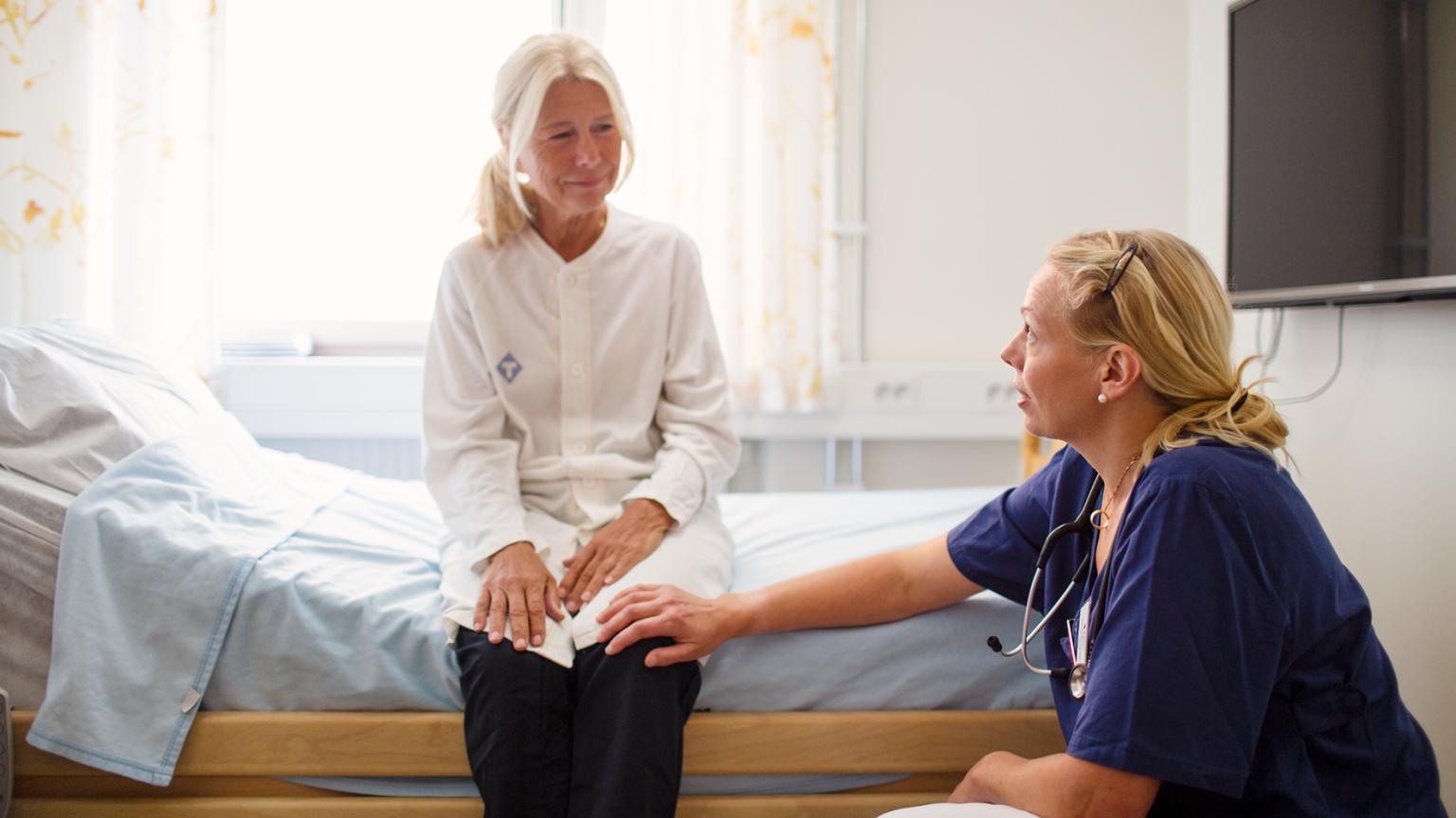 Linda Björkhem Bergman sitter på knä vid en patient. Foto: Martin Stenmark