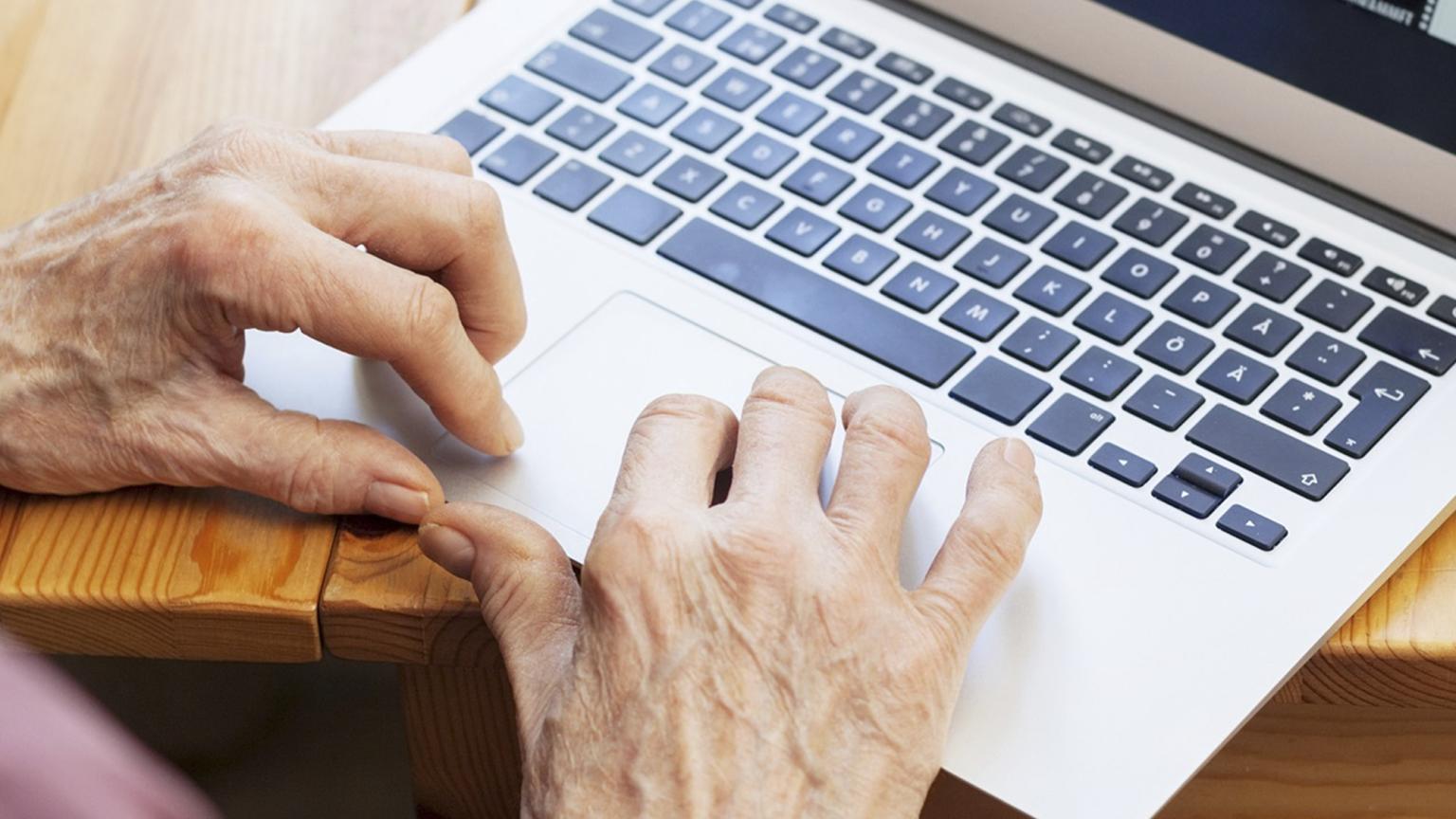 Äldre händer vid laptop