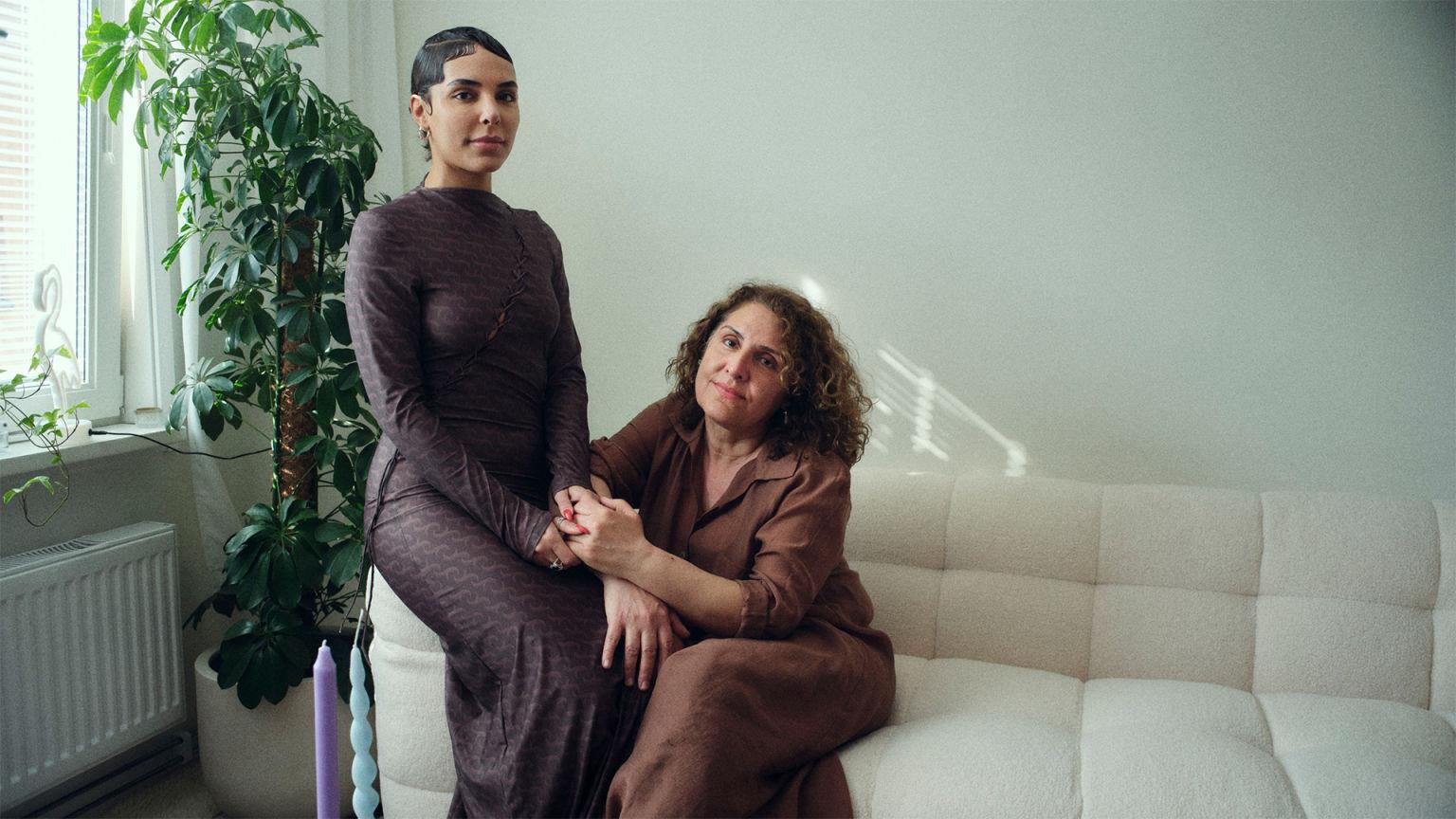 Två kvinnor, en mor och en dotter, sitter i en soffa.