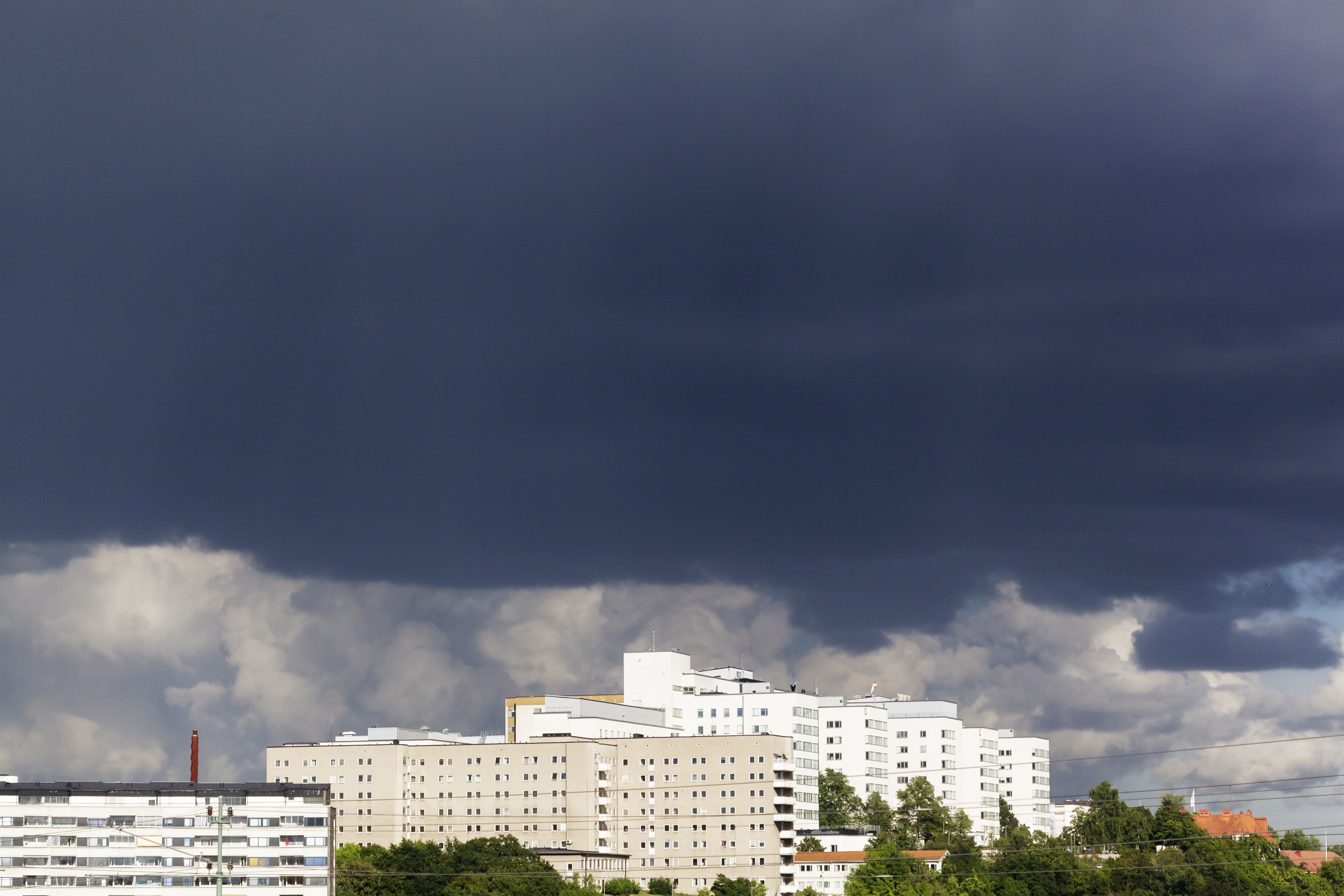 Tunga regnmoln över vita höghus.