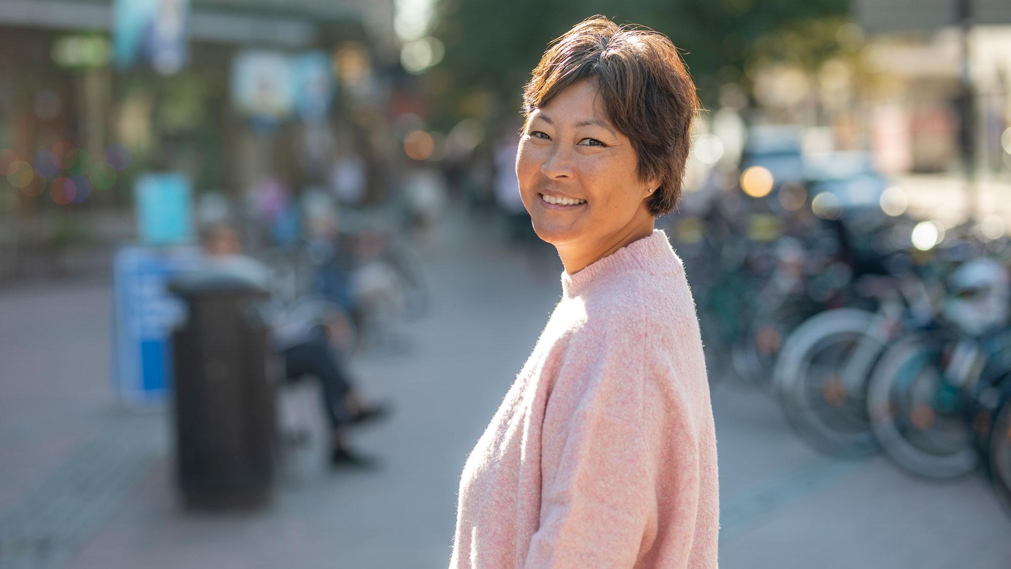 Helena Torsler Andersson, sjuksköterska på Cancerlinjen, står på ett en gågata i solen.