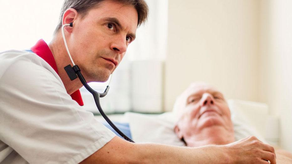 Läkare med stetoskop undersöker en man.
