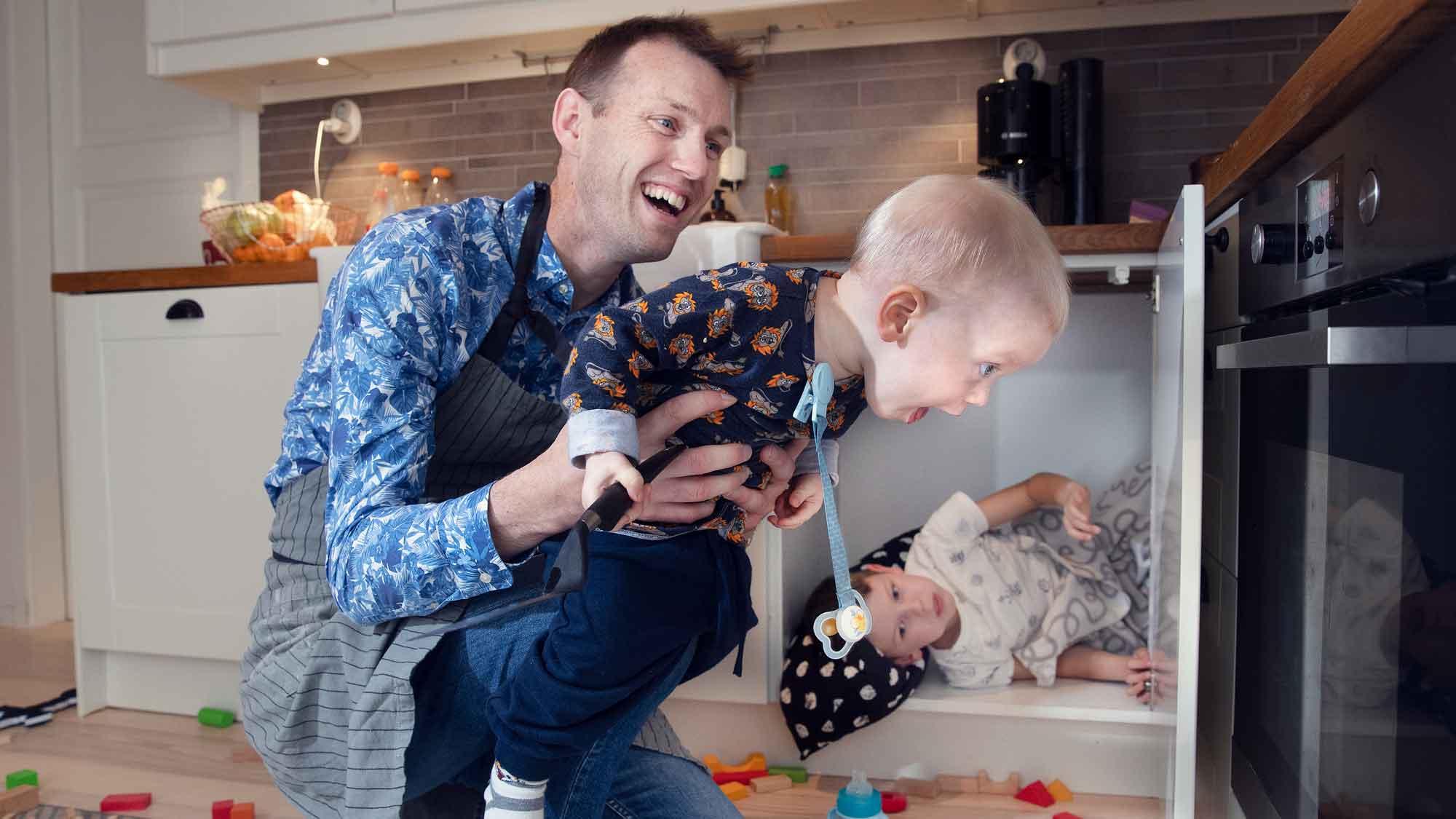 Pappa med sin två söner i köket