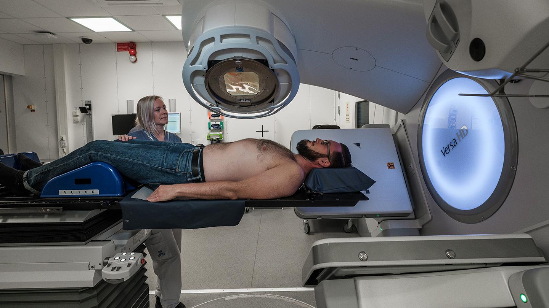 Patient ligger i ett behandlingsrum under en strålningsapparat.