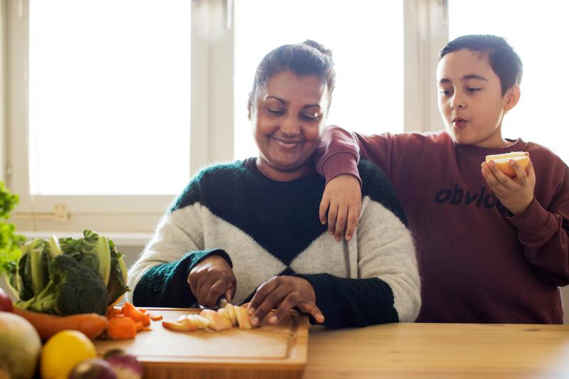 En kvinna sitter ner vid ett bord och skär upp grönsaker. Bredvid henne står ett barn med ett halvt äpple i handen.
