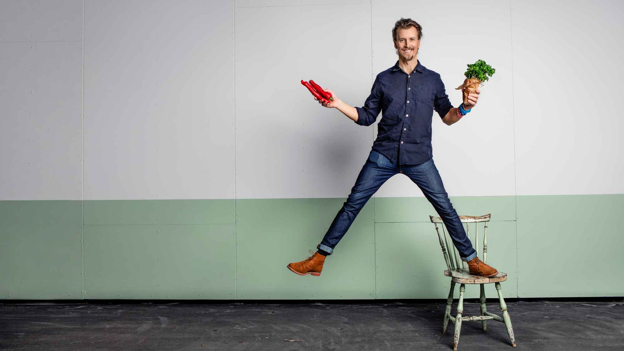 Cancerfondens ambassadör, kocken Paul Svensson, står och balanserar på en stol med grönsaker i händerna.