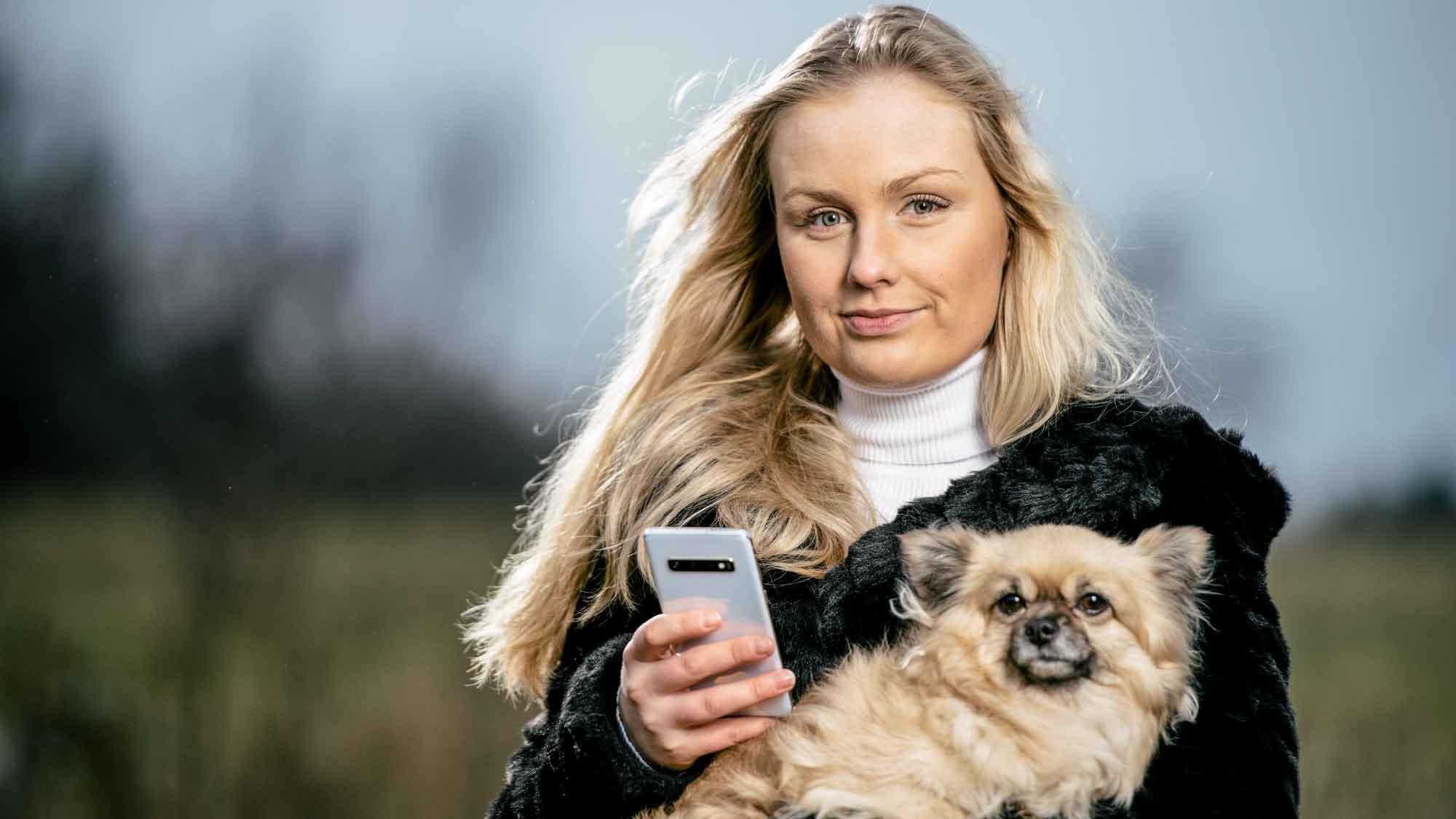 Cornelia Nilsson med sin hund och mobiltelefon