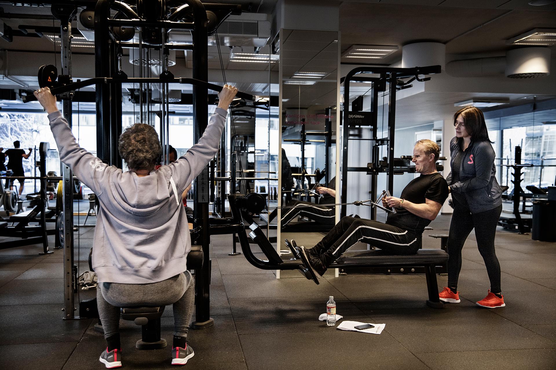 Från vänster till höger: Helena Rodensjö gör latsdrag i en maskin. Per Gradin tränar ryggen i en roddmaskin på SATS. Han får hjälp av en personlig tränare.
