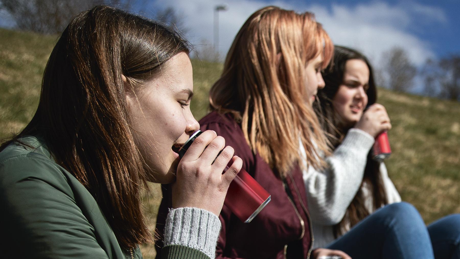 Tre tjejer sitter och dricker läsk