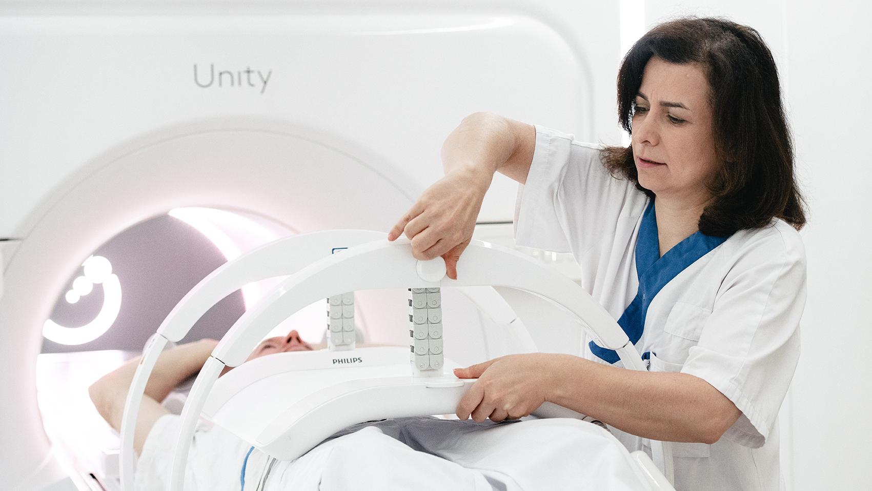 kvinna som justerar en del av en strålningsmaskin