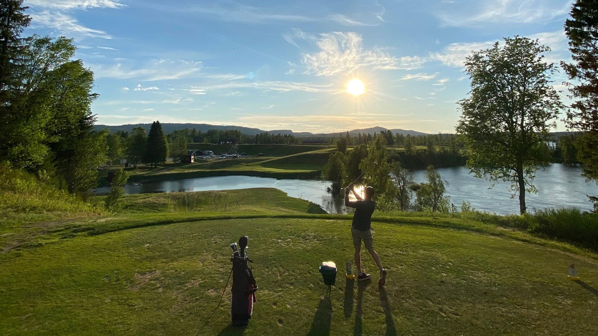Man på golfbana i solnedgång
