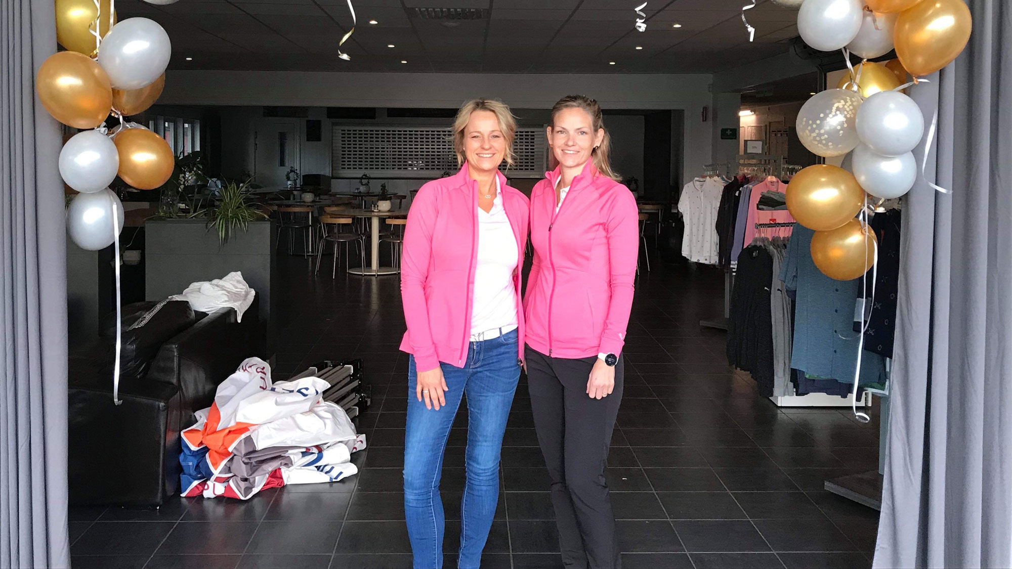 Två kvinnor i rosa tröjor i en dörröppning med ballonger