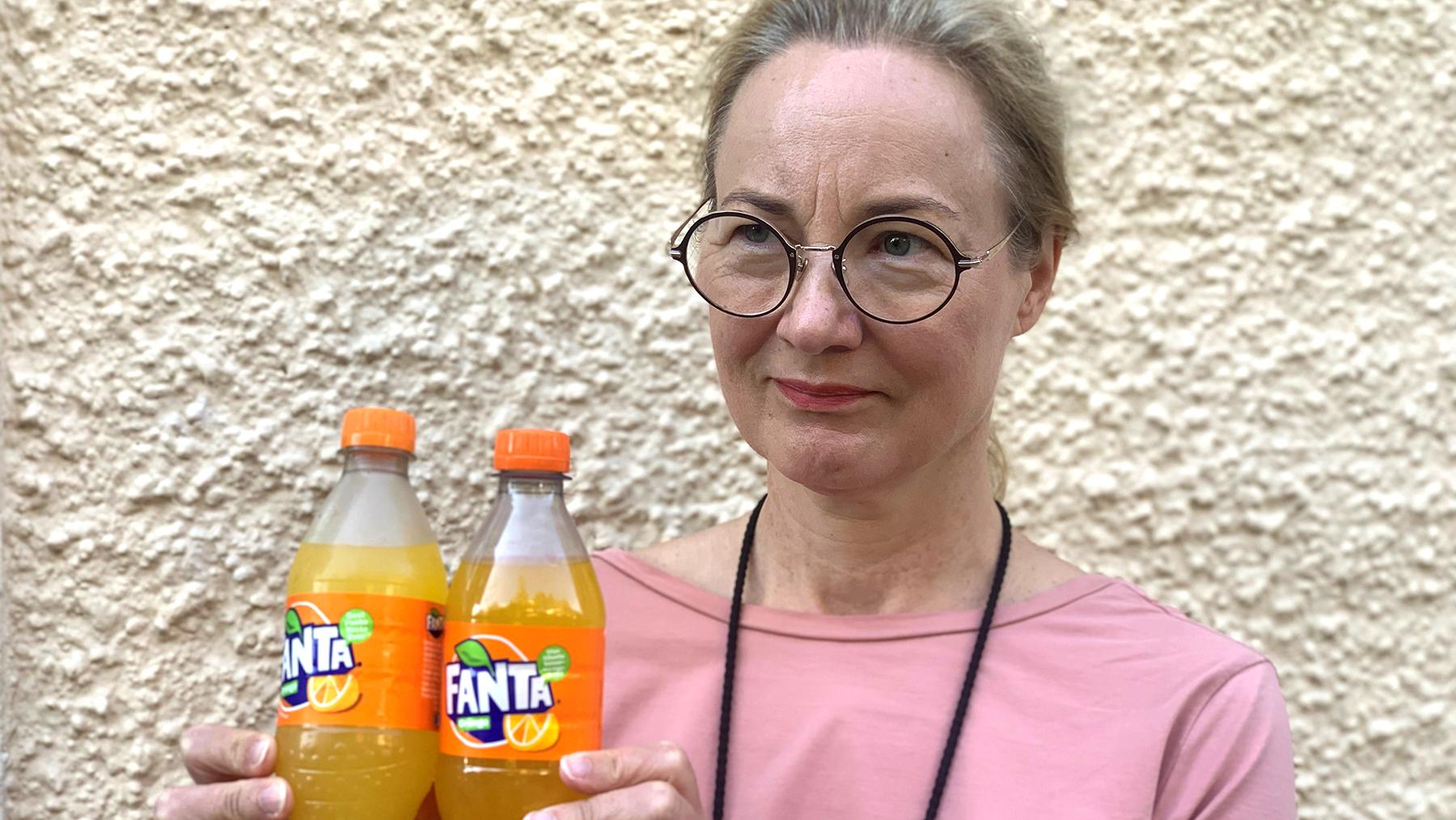 Cancerfondens generalsekreterare Ulrika Årehed Kågström håller upp två flaskor med fanta.