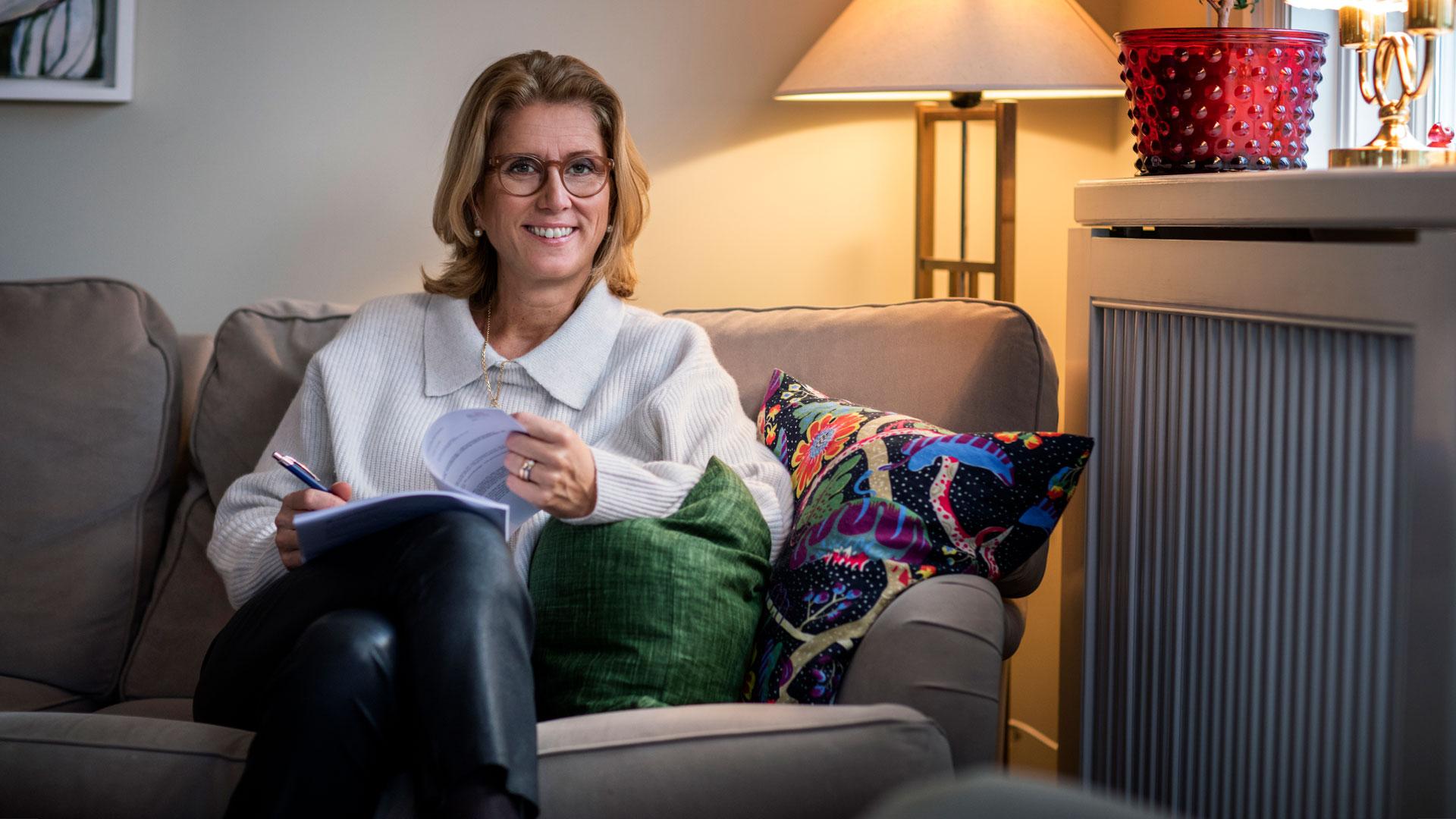 Kvinna läser i soffa.