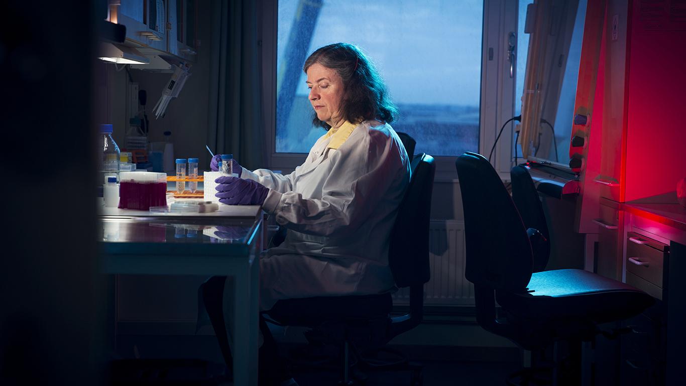 Kvinna i labbrock vid labbänk.