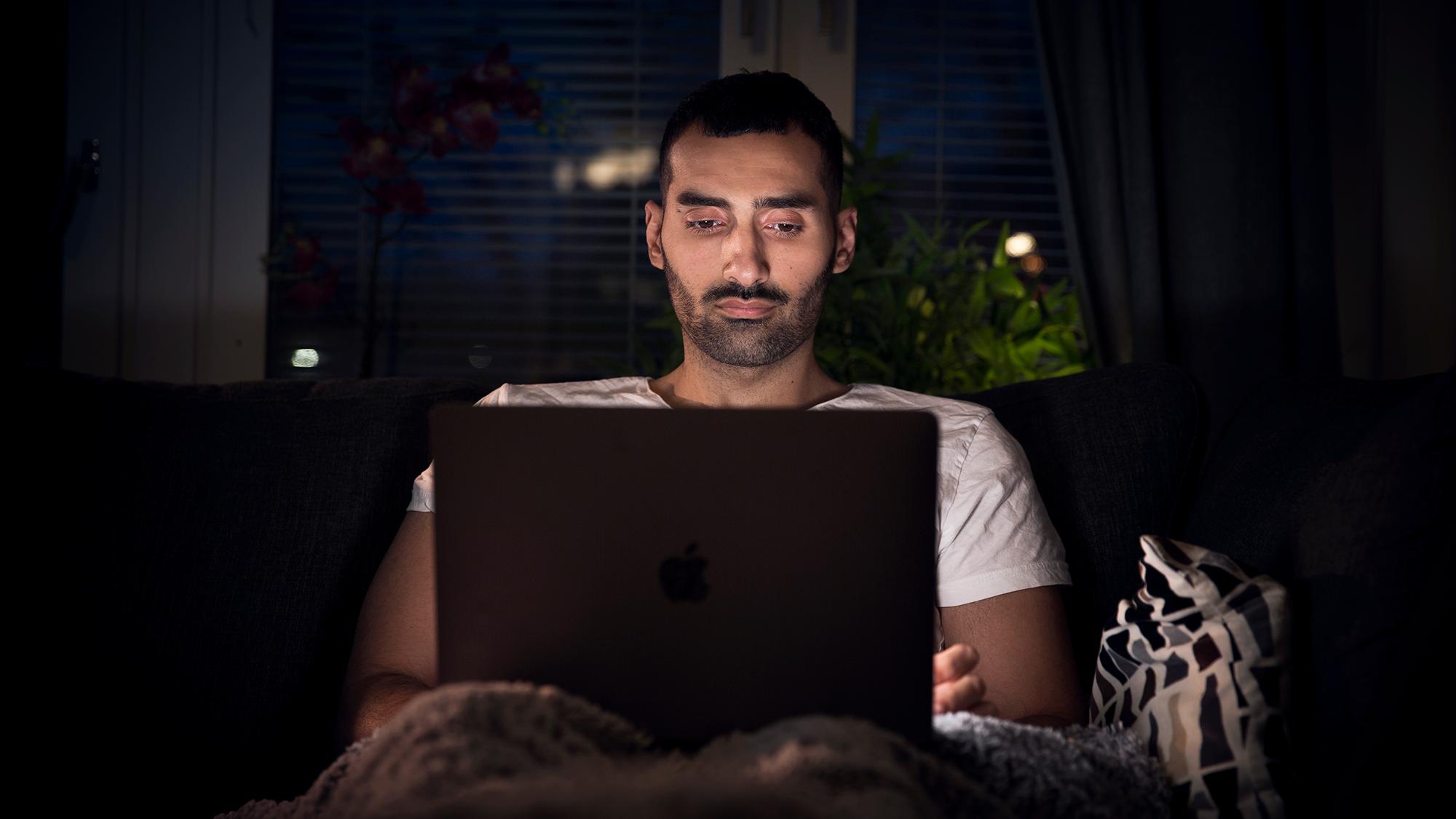 Ahmed Jalal sitter i soffan med datorn i knät