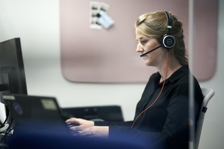 Fanny Pontan som jobbar på Cancerlinjen sitter vid en dator.