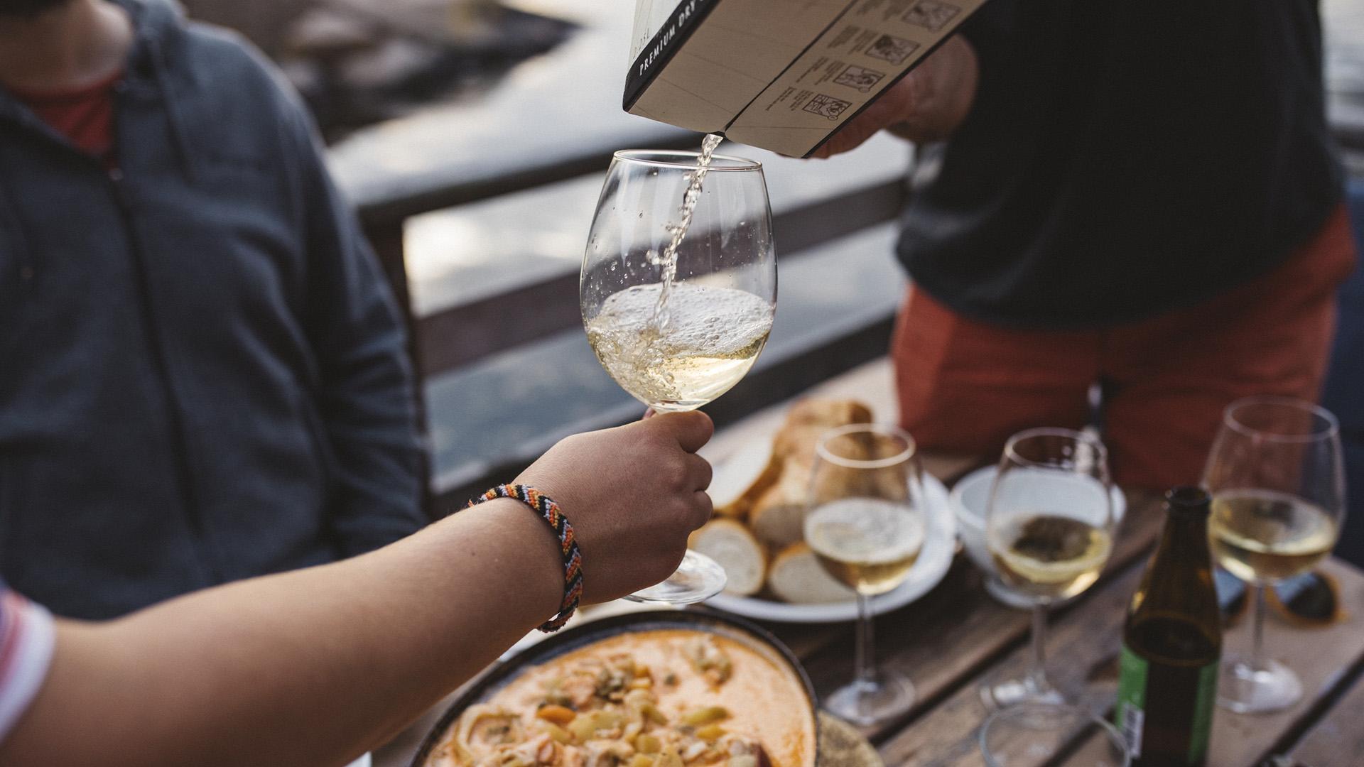 En person häller upp vitt vin från en bag-in-box i ett glas. I bakgrunden finns tallrikar med mat.