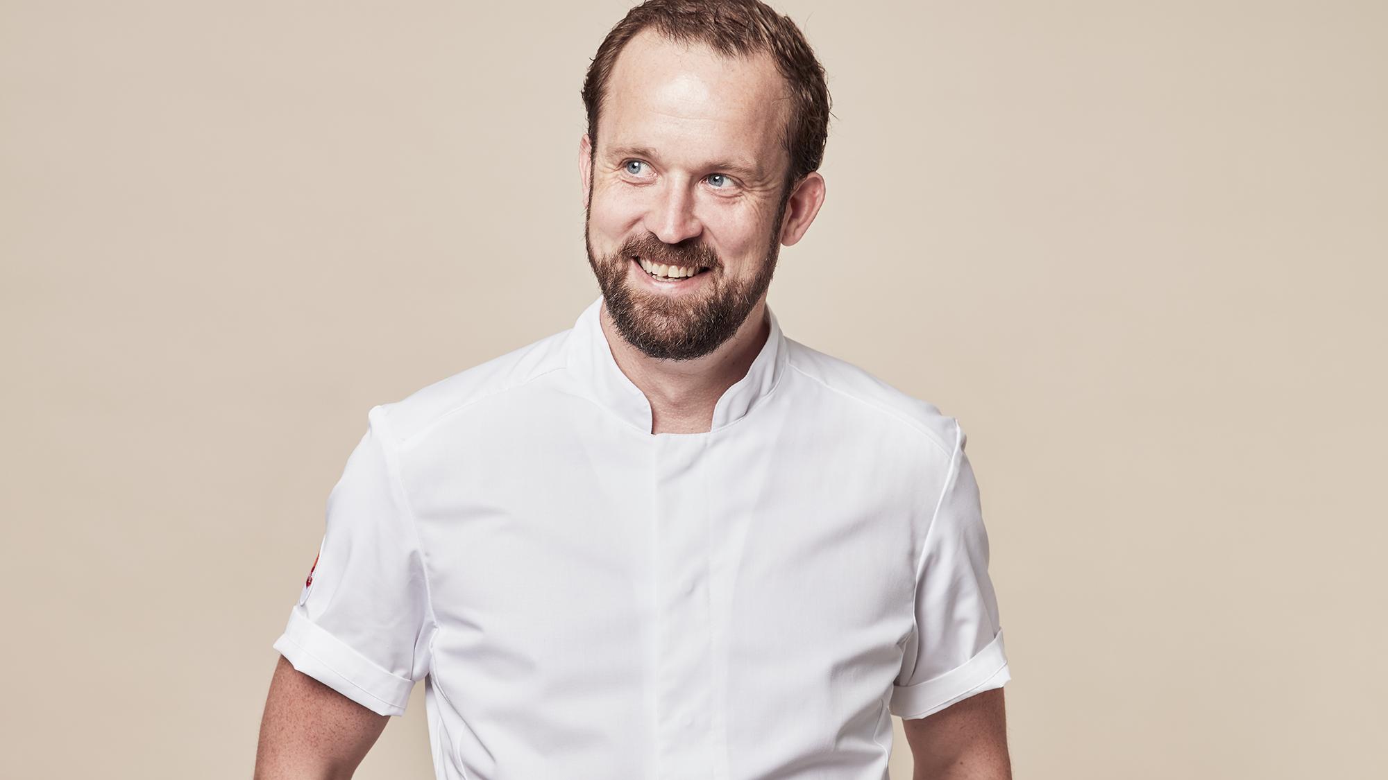 En porträttbild på Alexander Sjögren när han står i sin kockjacka.