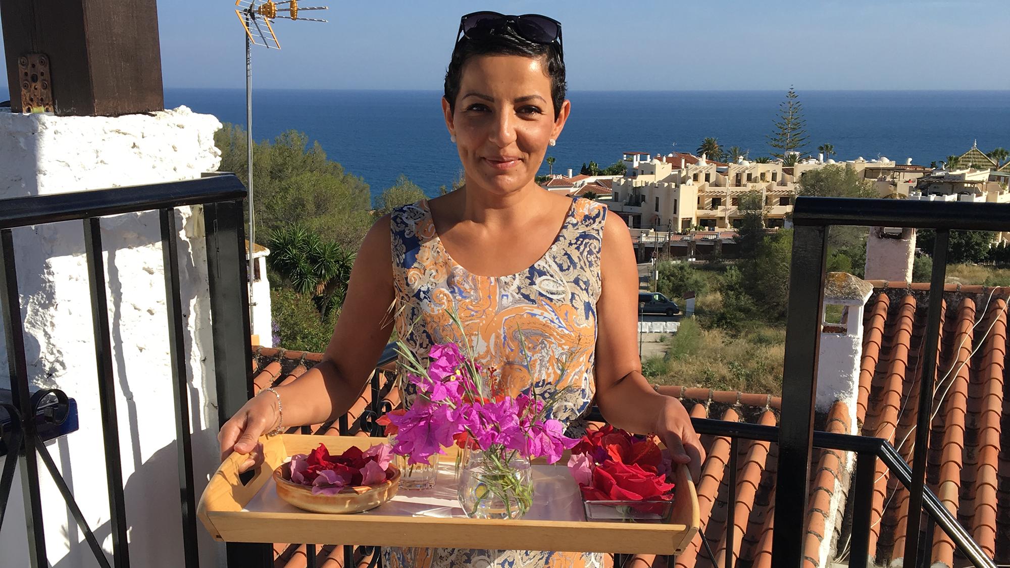 Hero Baqay håller i en bricka med blommor på en terass
