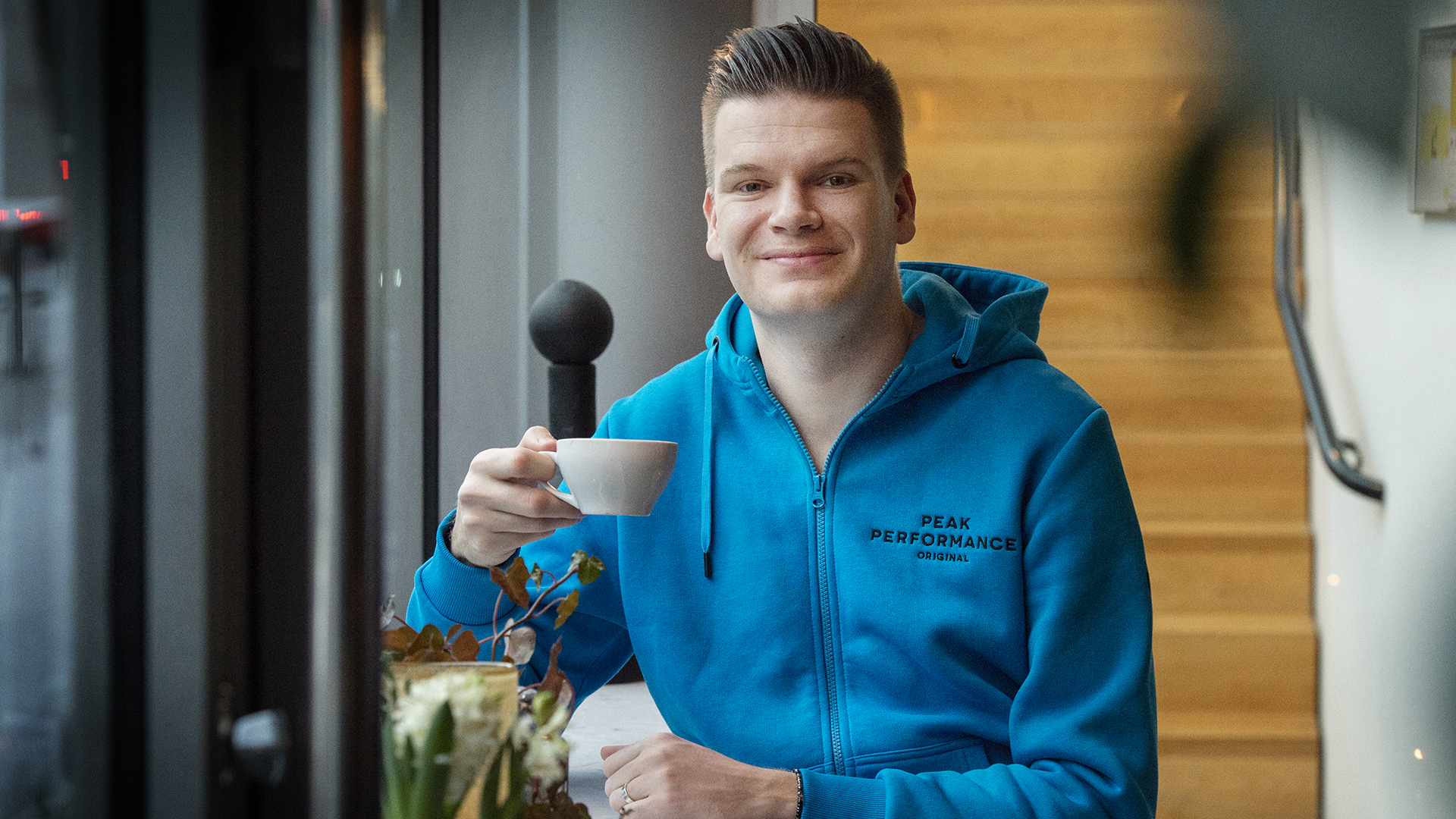 Porträtt på Johan Havskog där han sitter med en kopp kaffe i handen.