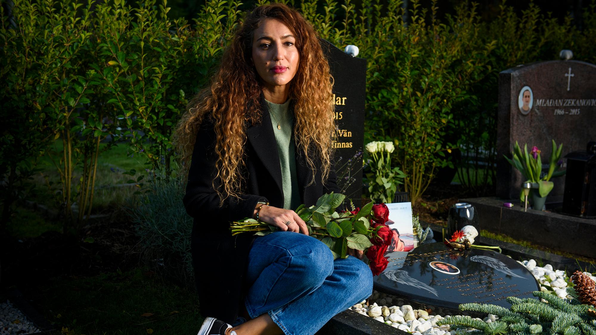 Bijana Theanoar sitter vid sin syster Servas grav i Göteborg med en bukett röda rosor i handen.