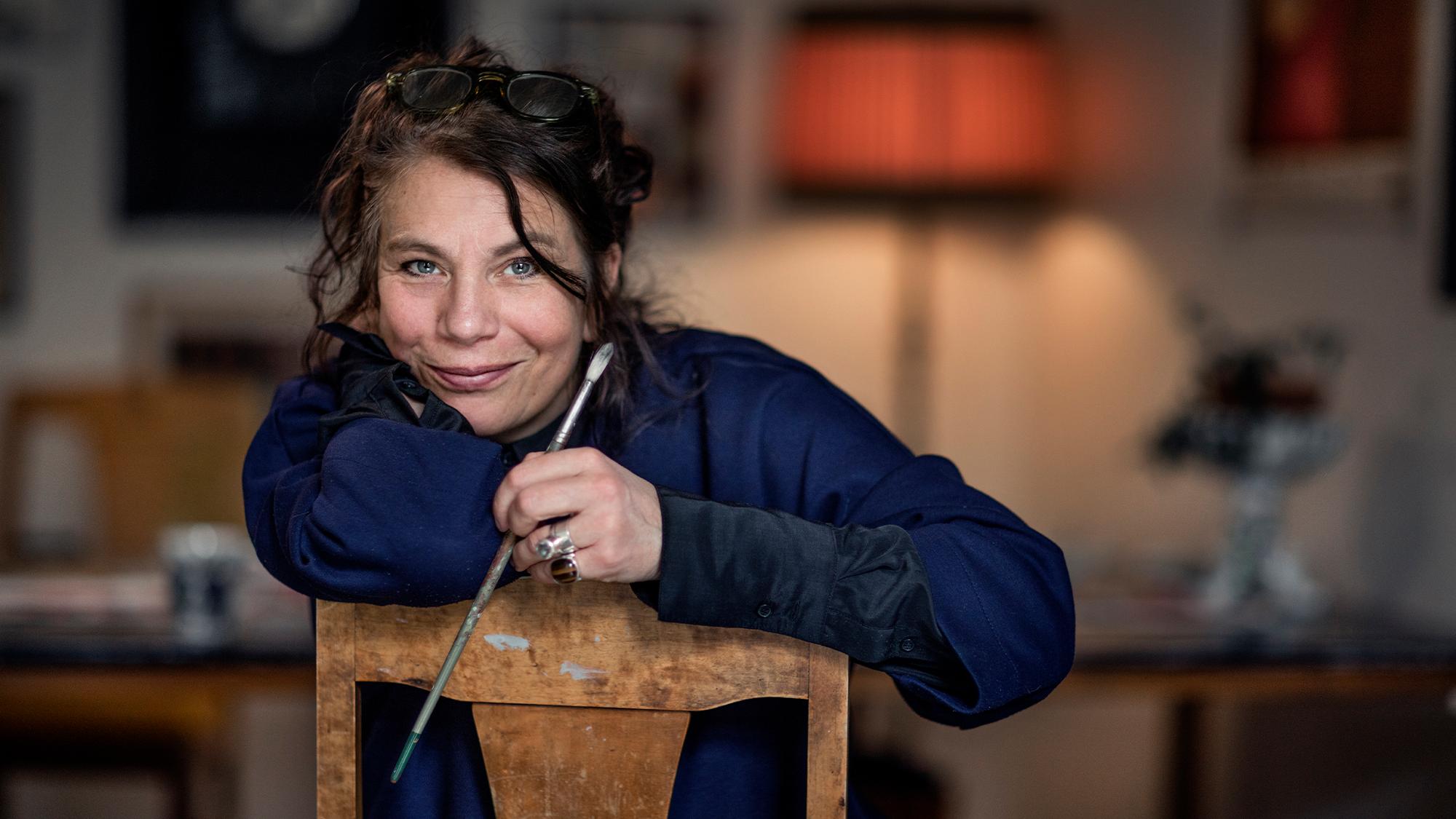 Åsa Öhrn sitter på en stol med en pensel i handen och tittar in i kameran.
