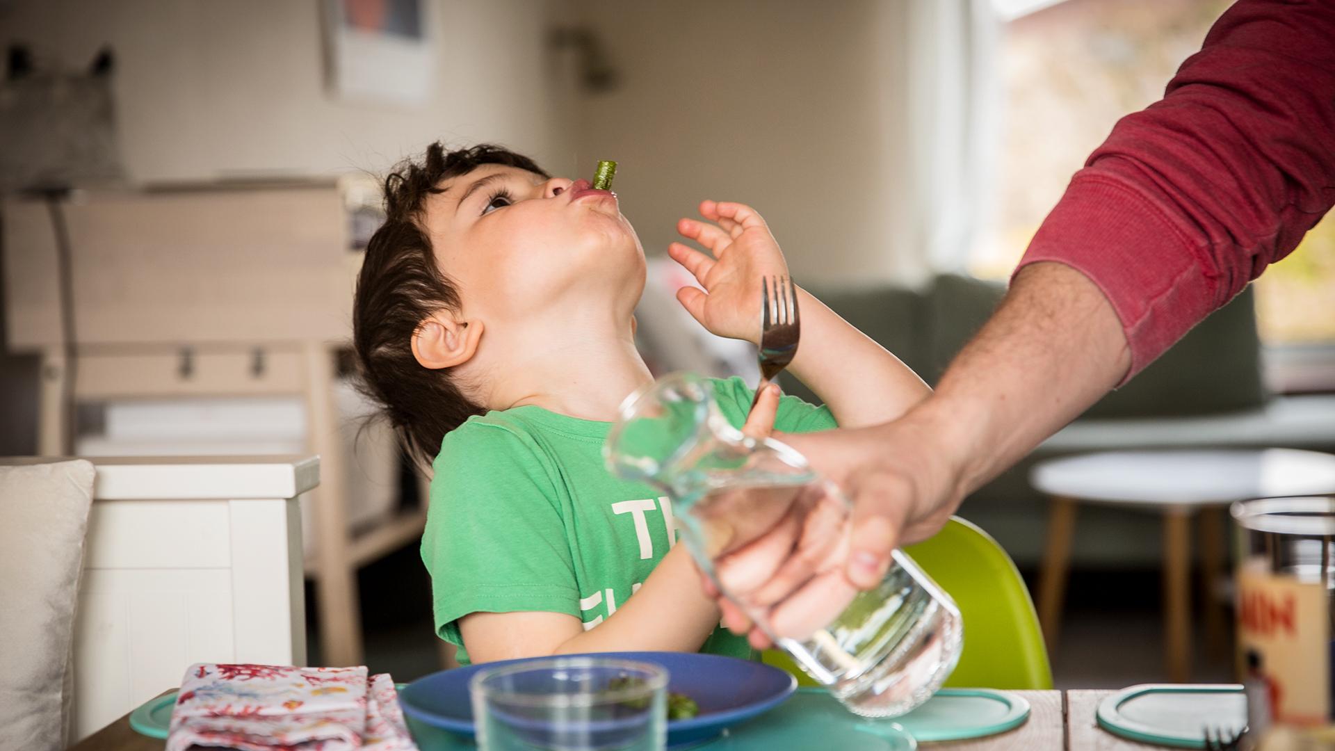 Ett barn sitter vid matbordet och äter sparris.
