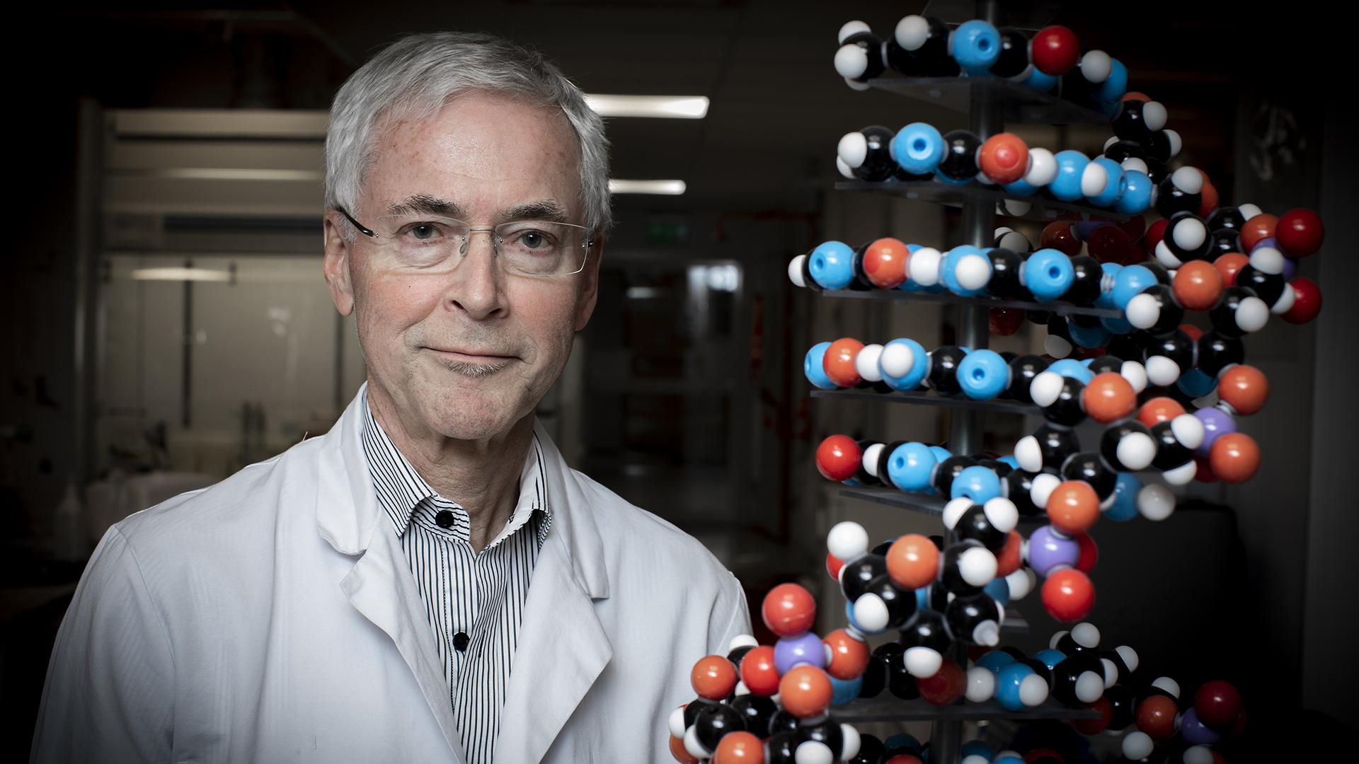 Professor Edvard Smith bredvid en DNA-spiral i sitt labb på Karolinska Universitetet i Huddinge.