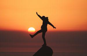 man balancing on rock sunset
