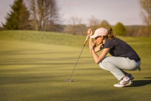 Woman studying golf on green
