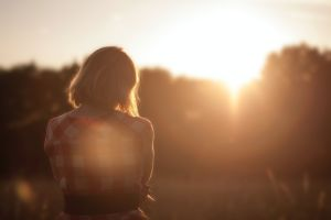 Woman looking out to morning sunshine