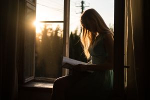 Woman reading book in sunlight