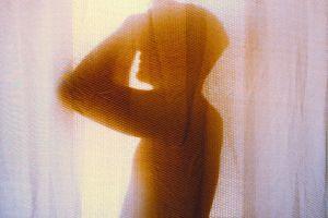man holding head in sunlight behind window