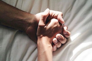 Two people holding hands in bed