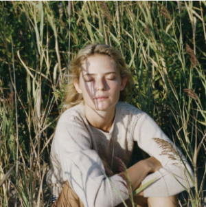 A lady sitting in long grass