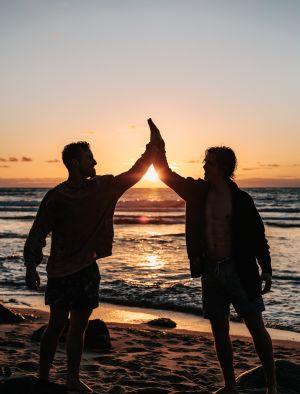 Men high fiving on beach
