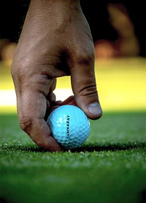 Man holding Cannaray CBD golf ball