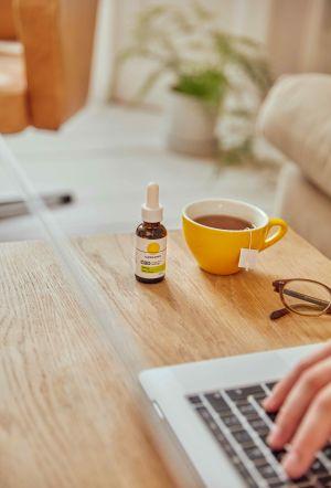 Cannaray CBD Oil next to tea & laptop