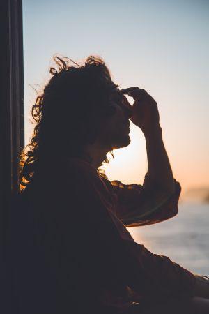 Woman looking outside window in pain