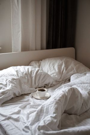 Unmade bed with cofeee