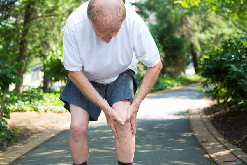 Older man suffering from osteoarthritis in his knee.